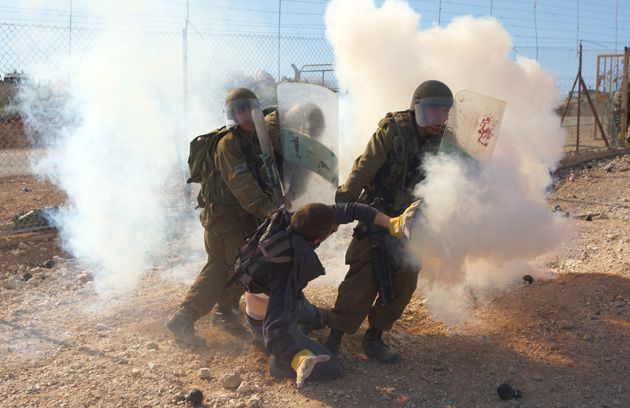 Confrontation: Israeli soldiers grab an activist during a weekly protest at Bil?in. Palestinians say demonstrators peacefully resist, while Israelis contend that violent riots often occur.