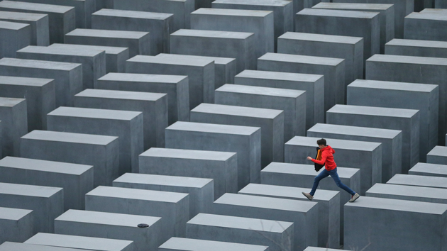 Child jumping over the Memorial to the Murdered Jews of Europe in Berlin