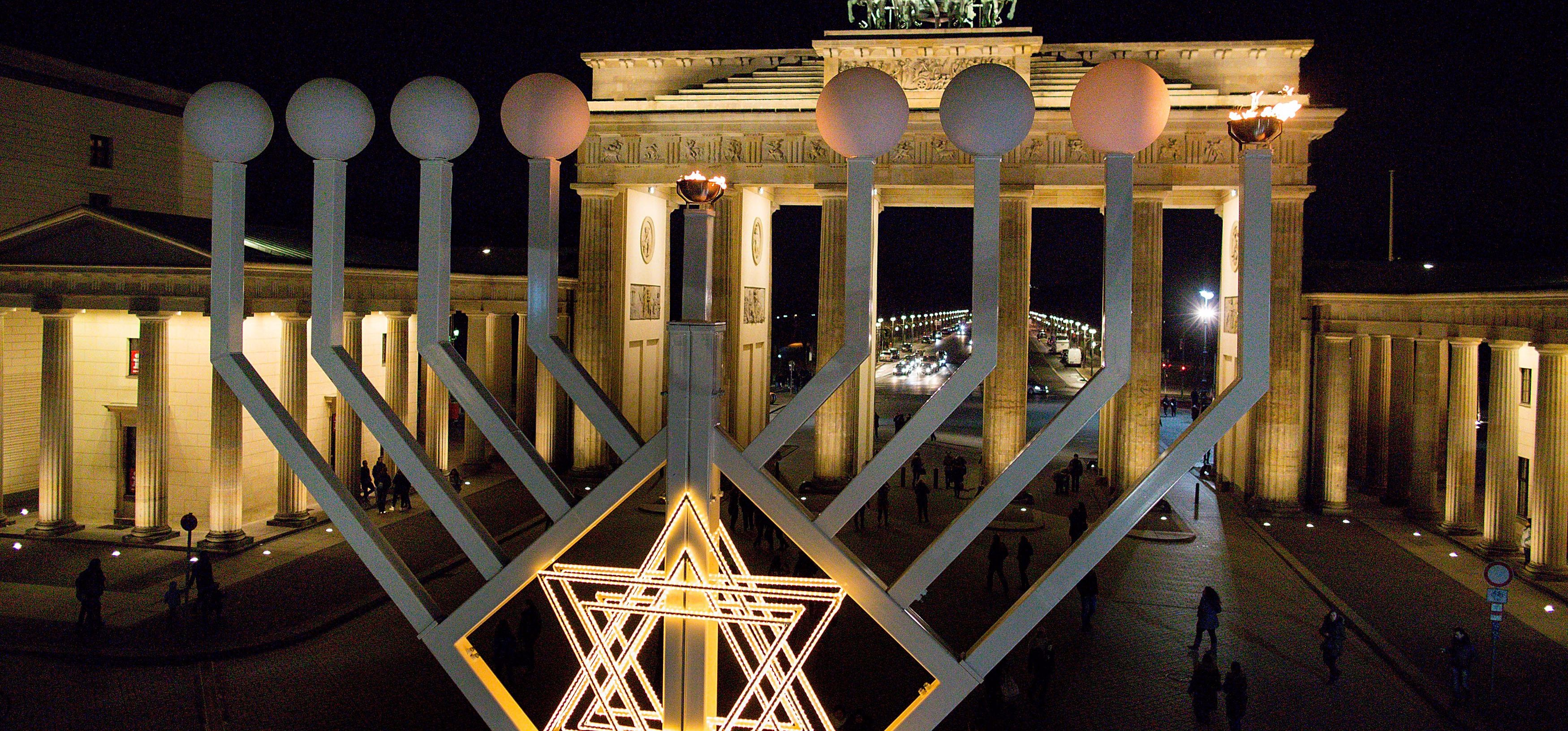 A group of Syrian refugee children — along with other Muslim groups in Berlin — joined with Jewish groups for a public Hanukkah candle-lighting ceremony t the Brandenburg Gate.