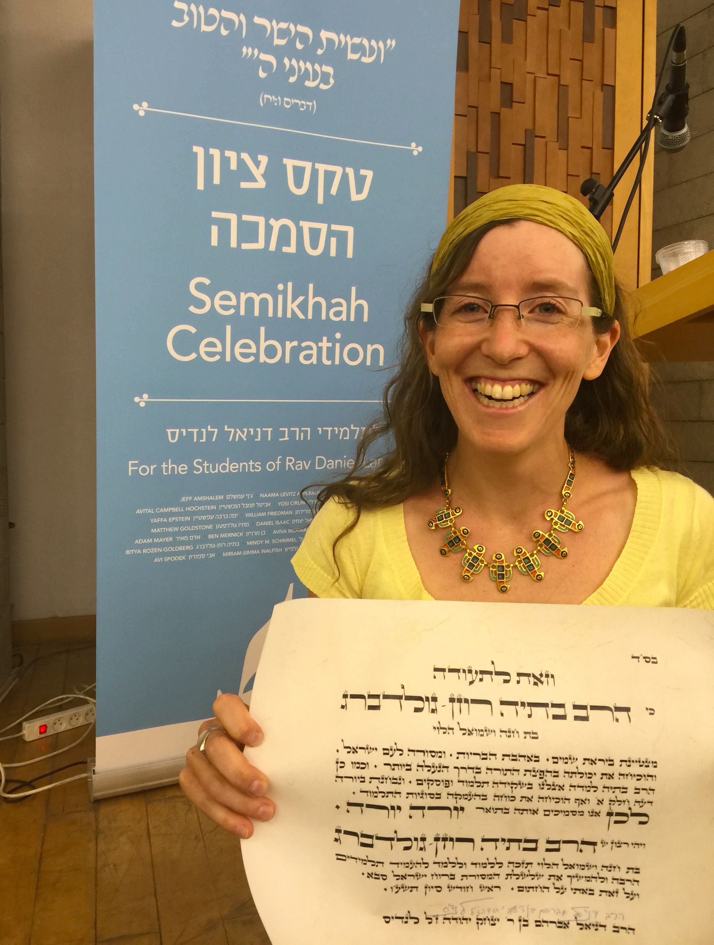 Bitya Rosen-Goldberg holds up her rabbinic ordination certificate.