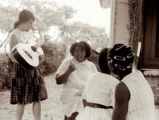 Heather Booth plays guitar for Fannie Lou Hamer during the Freedom Summer Project in Mississippi, 1964.