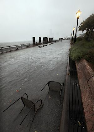 Water from New York Harbor washes over a sidewalk in Battery Park on August 27.