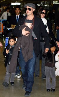 BABIES IN TOW: Superstars Brad Pitt and Angelina Jolie race through an airport with their ever-exanding brood.