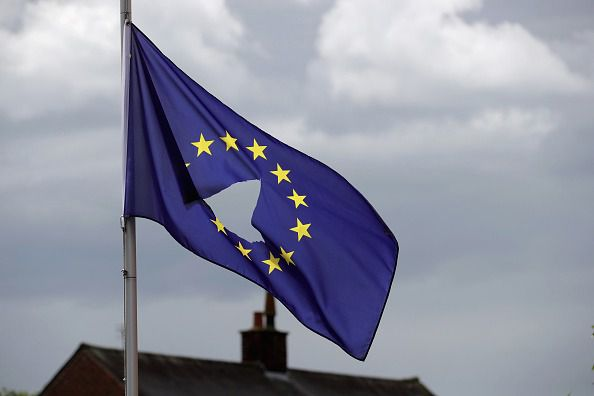 A European Union flag flies with a hole in the middle.