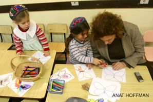 Children decorate paper butterflies as part of Sue Klau?s project.