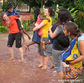 MUDDY WATERS: At an orphanage in Kampong Chhnang in central Cambodia American volunteers play with children in the post-monsoon murk.