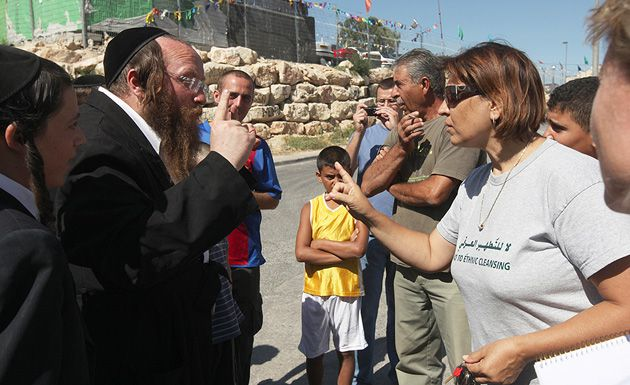 Whose Home?: A Palestinian protester, wearing a T-shirt saying ?No to Ethnic Cleansing,? confronts a Jewish man outside a disputed building in East Jerusalem.