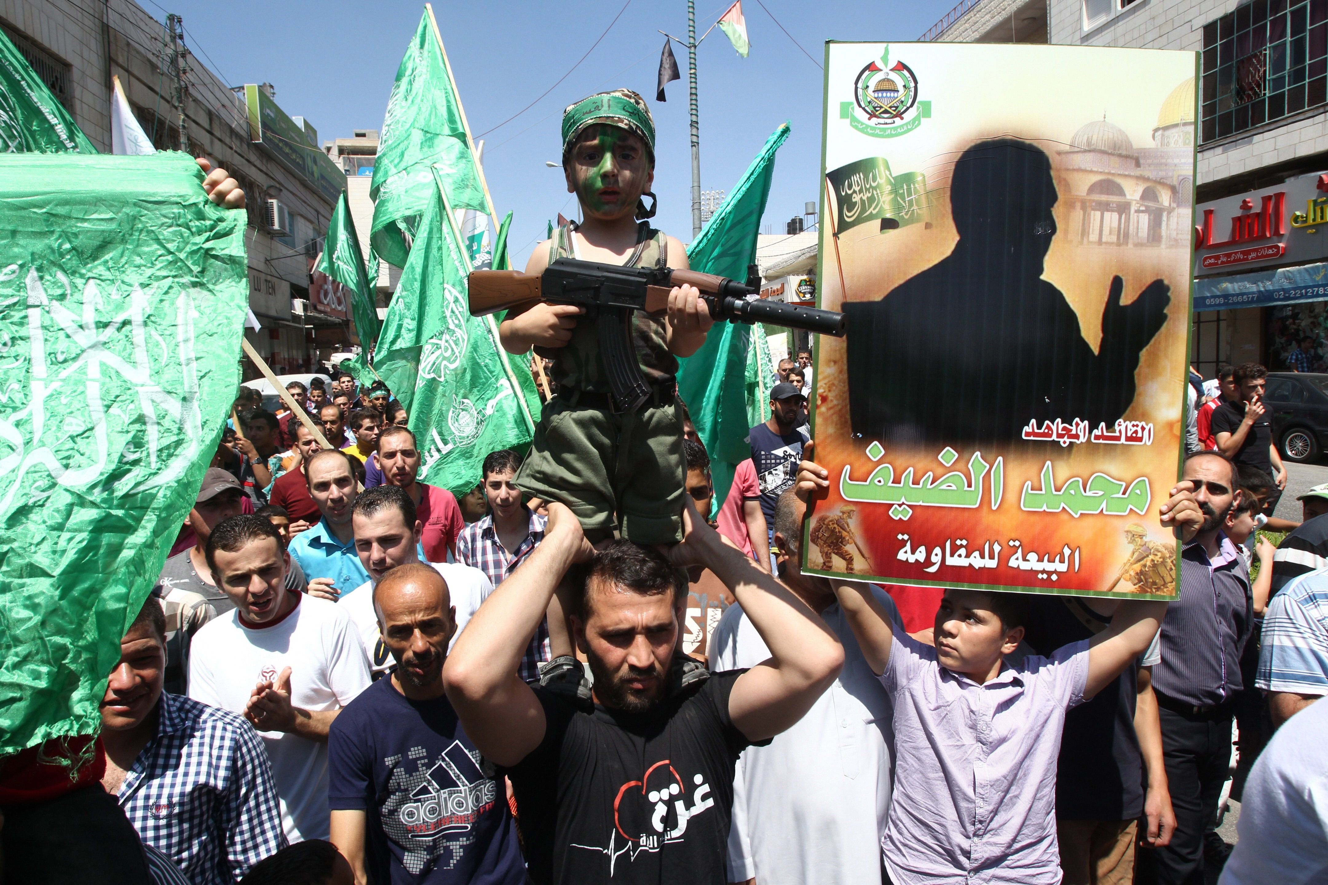Hamas supporters at a rally last summer hold up a picture of Mohammed Deif, the group's military chief.