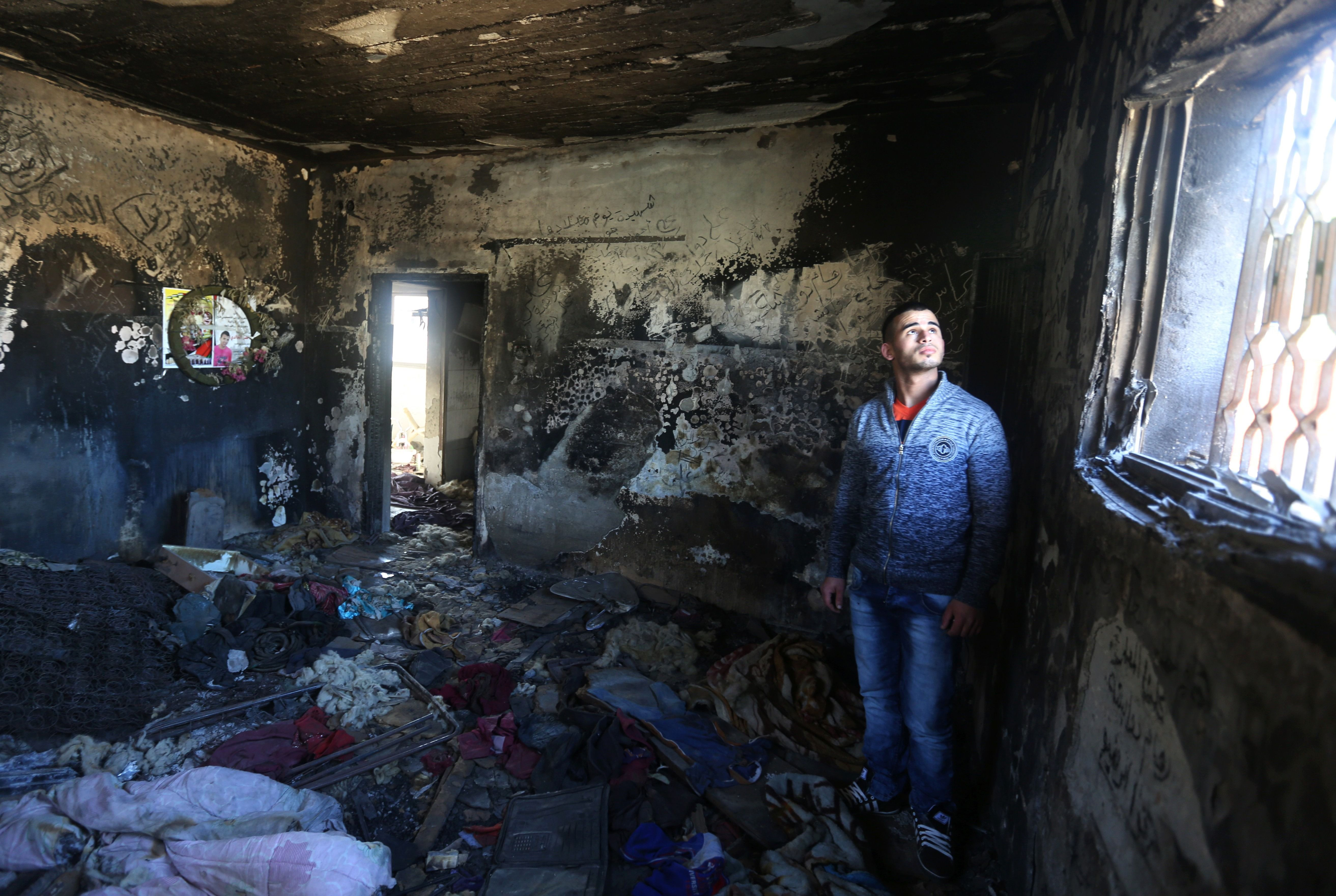 A relative stands in the burnt-out shell of West Bank home where a Palestinian family was killed in a firebomb attack by suspected Jewish extremists.