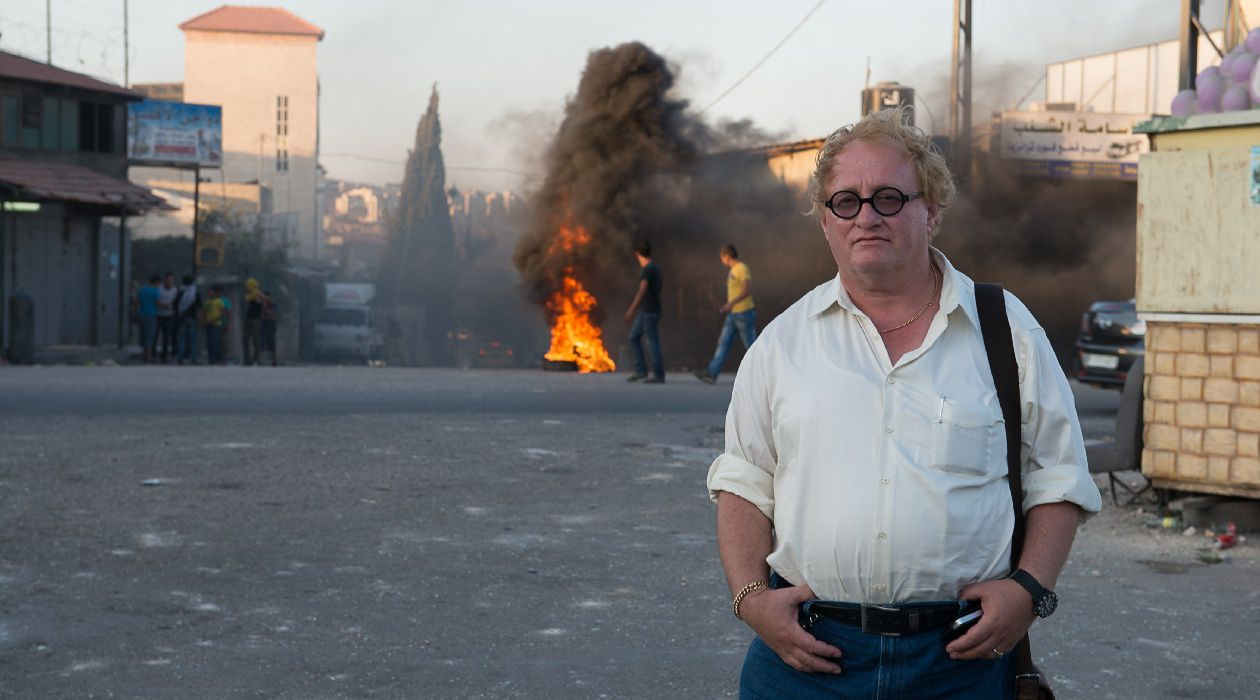 Cool Guys Don't Look at Explosions: Tuvia Tenenbom pauses for a photo during recent unrest in Israel.