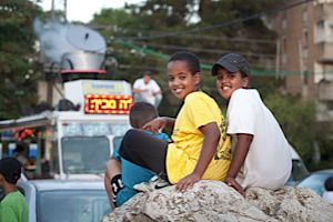 Local kids watch the scene that gathers around the AutoOchel in the Katamonim neighborhood in Jerusalem.
