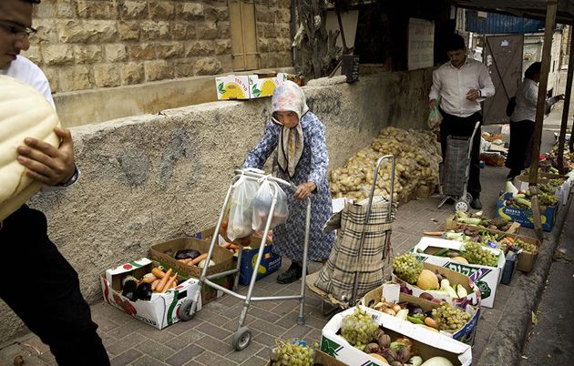 Want Amid Plenty: An elderly Jewish woman walks amid boxes of food that were intended for distribution to the poor and needy for Rosh Hashanah. New statistics show increasing numbers of Israelis relying on such services.