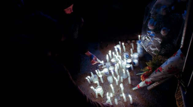 A woman lights a candle at the scene of a fire that killed seven Jewish children in Brooklyn.