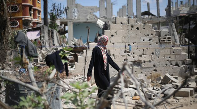 Broken: A Palestinian woman walks past a destroyed house in Khan Yunis in the southern Gaza Strip on September 11.
