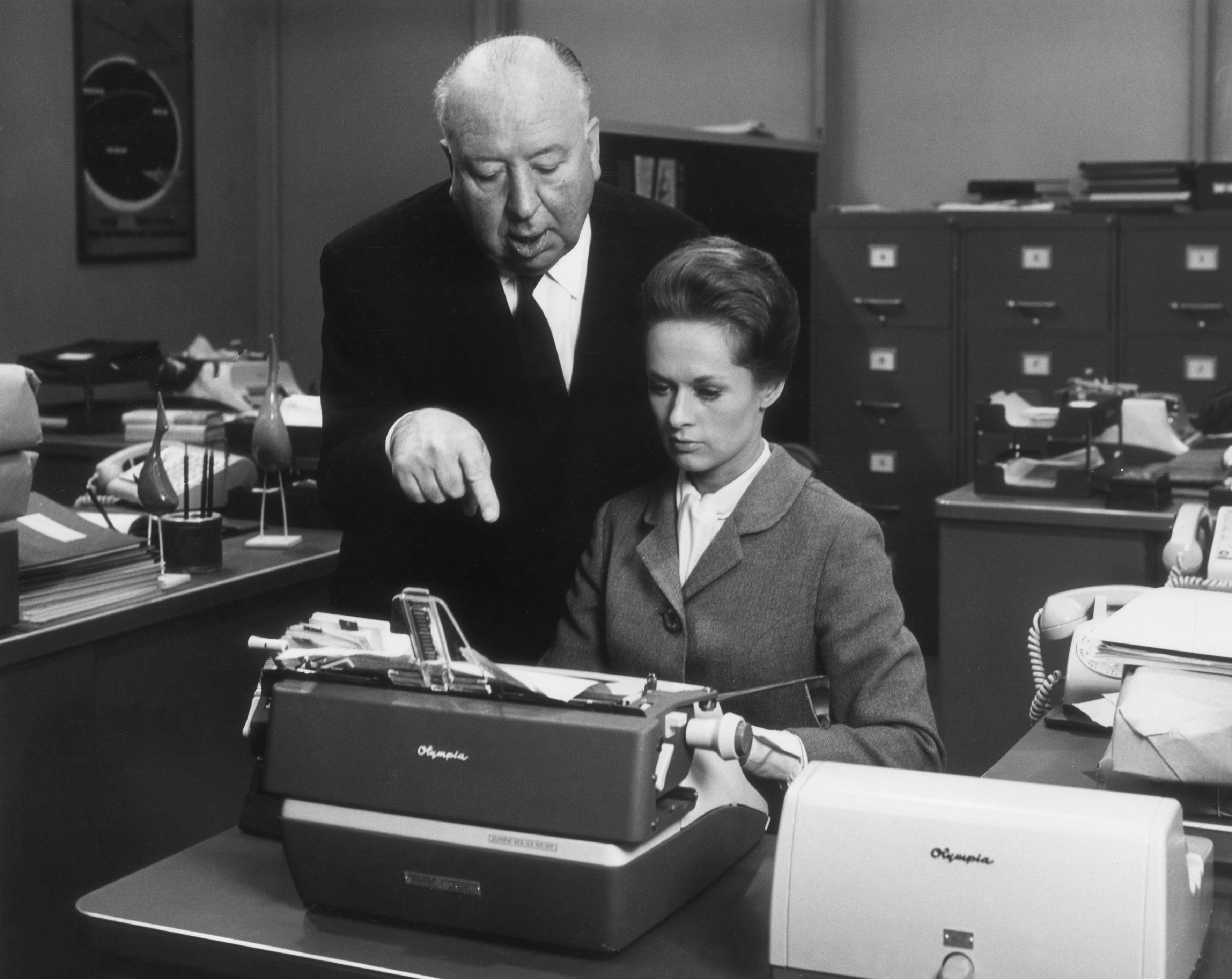 British director Alfred Hitchcock directs American actor Tippi Hedren while she sits in front of a typewriter on the set of his film, 'Marnie'.