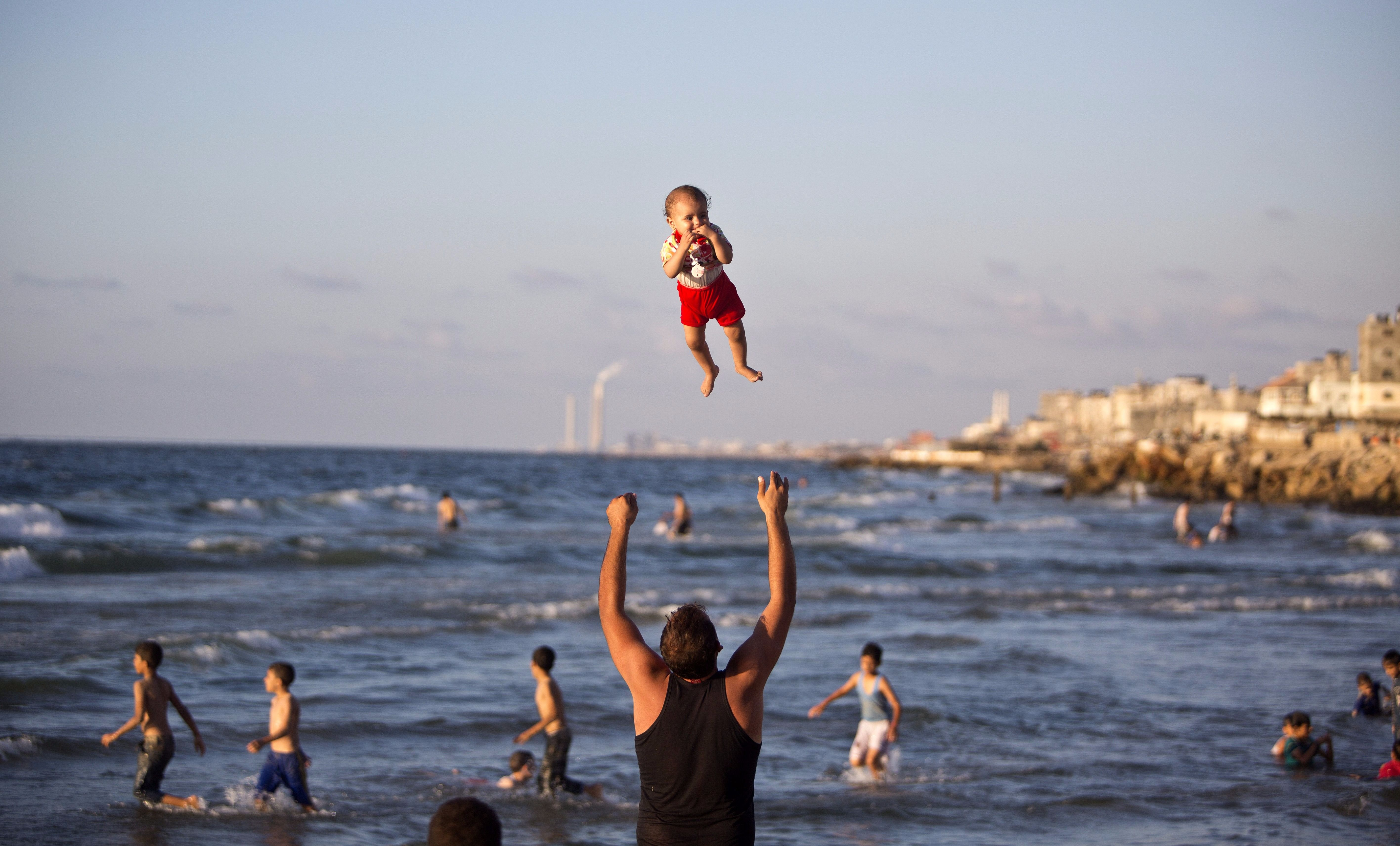 A Palestinian man plays with his baby on a beach in the Gaza Strip.