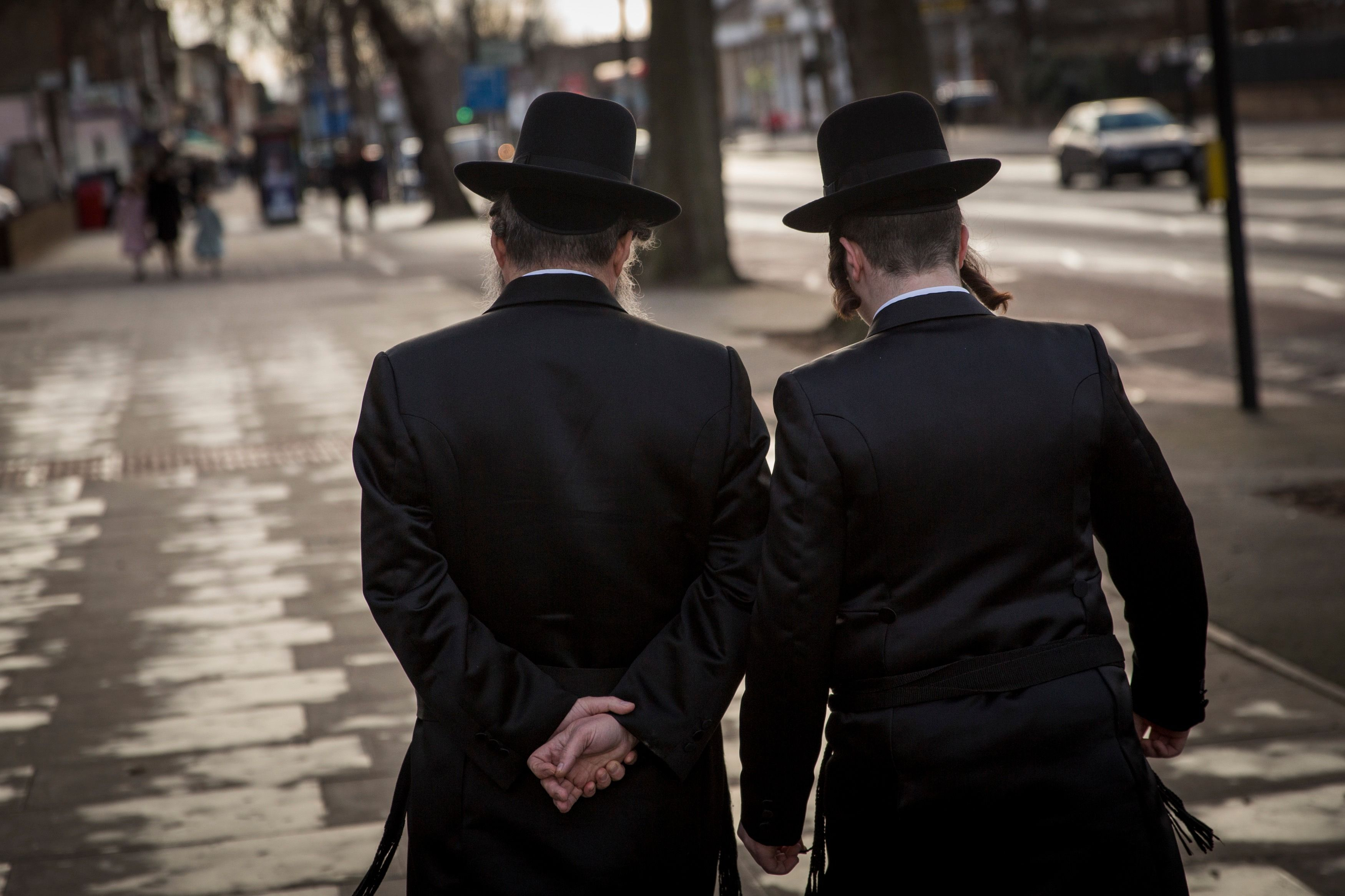 Two Hasidic men walk through the Stamford Hill neighborhood of north London.