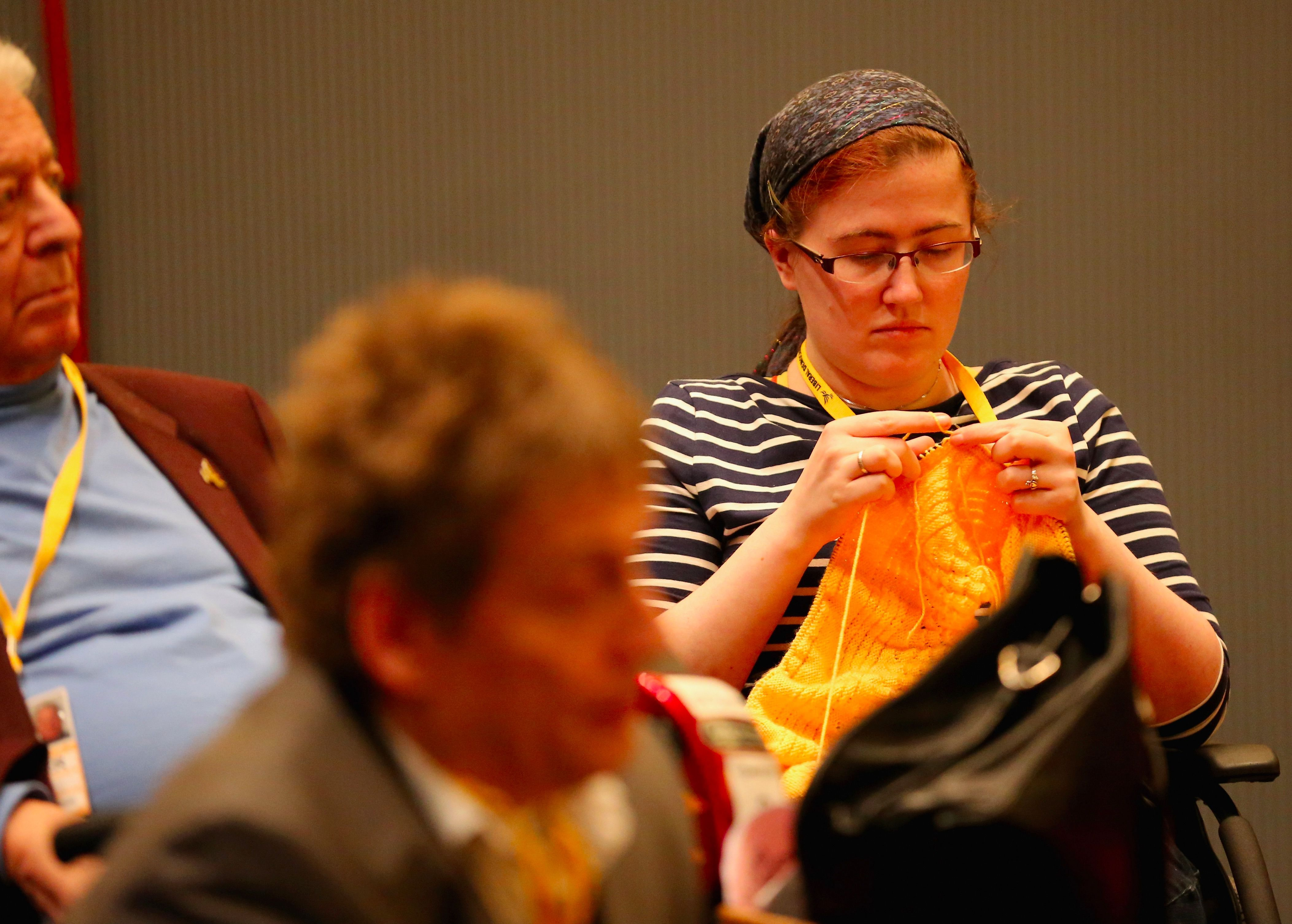A woman knits at the Liberal Democrat Spring Conference in Liverpool, England.