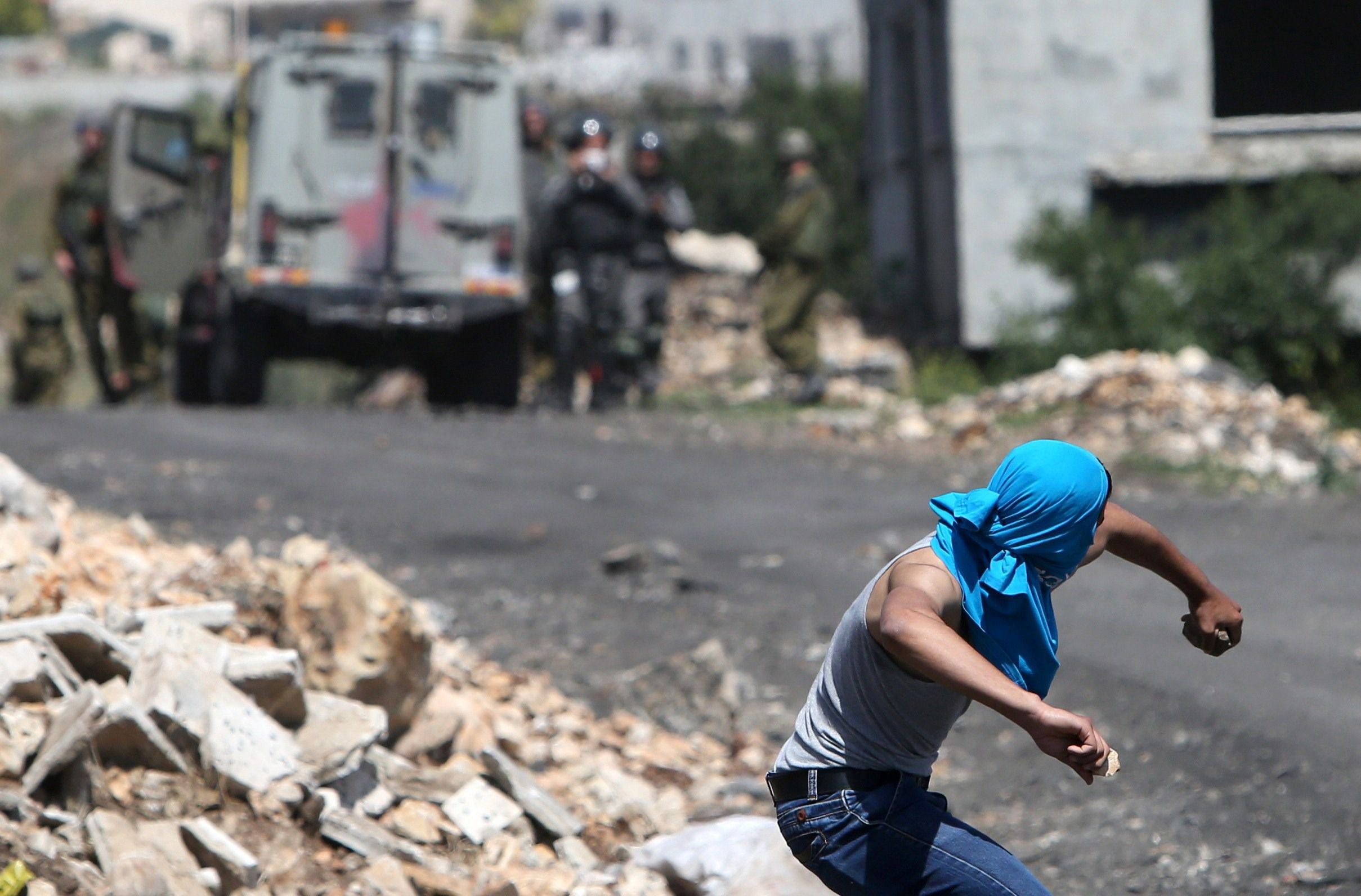 A Palestinian protestor throws stones towards Israeli security forces in May, 2015.