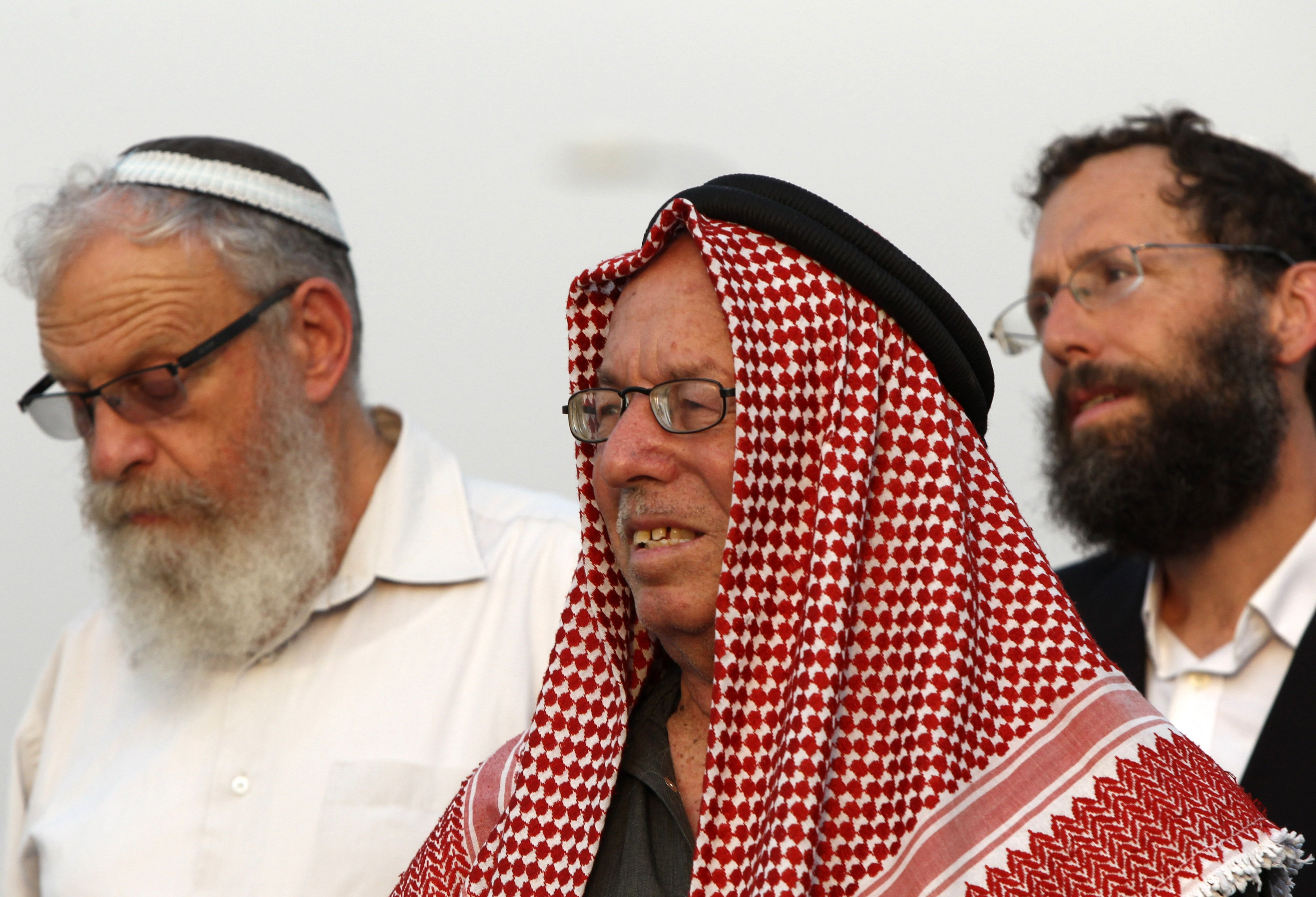 Palestinian peace activist Haj Ibrahim Abu el-Hawa and Jewish settlers attend a rally called for by the Israeli Tag Meir (Light Tag) organization, which denounces racism and calls for peace between Palestinians and Israeli settlers in the occupied Palestinian territories.