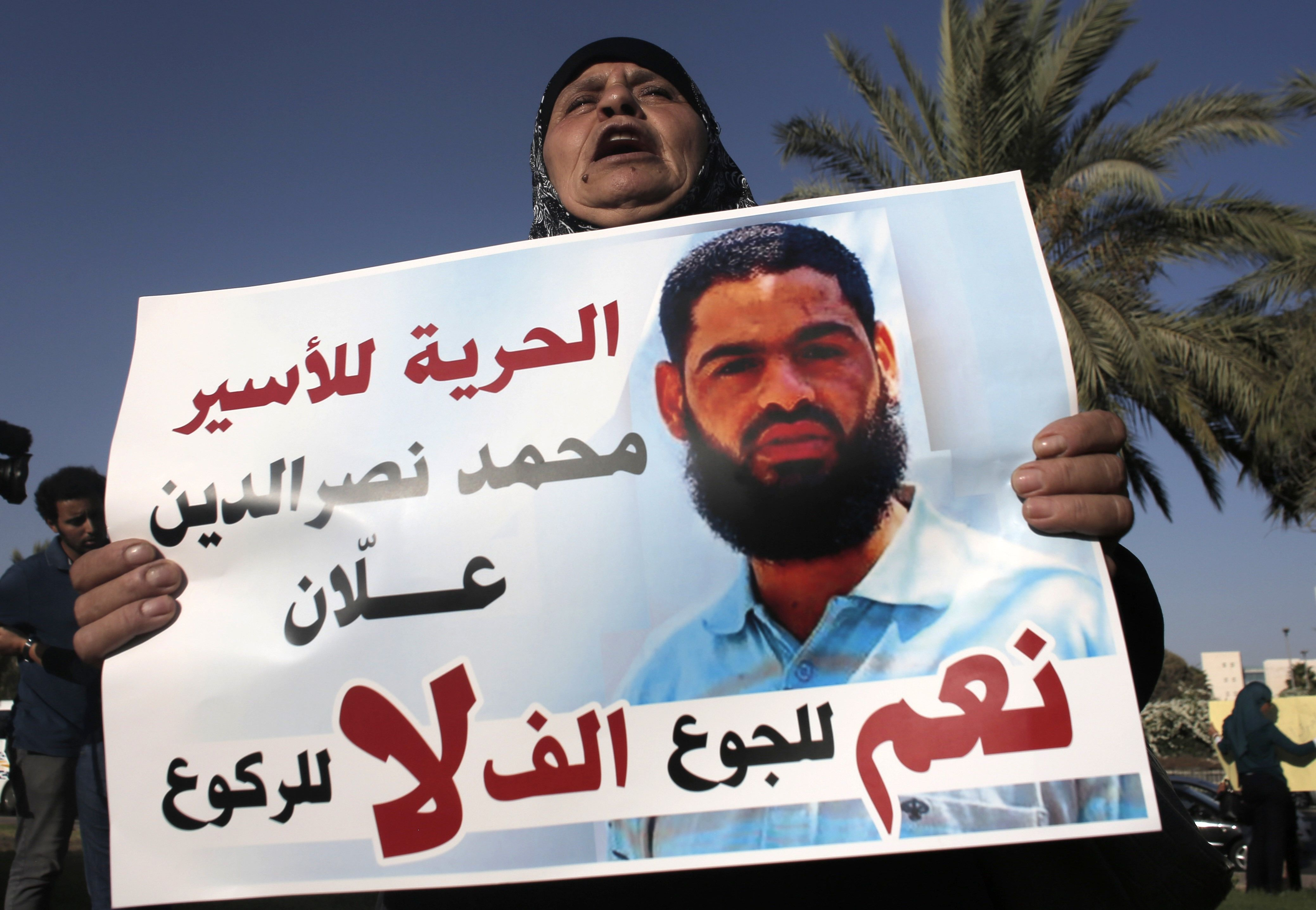 Mother of Mohammed Allaan holds a portrait of her son during a rally calling for his release.