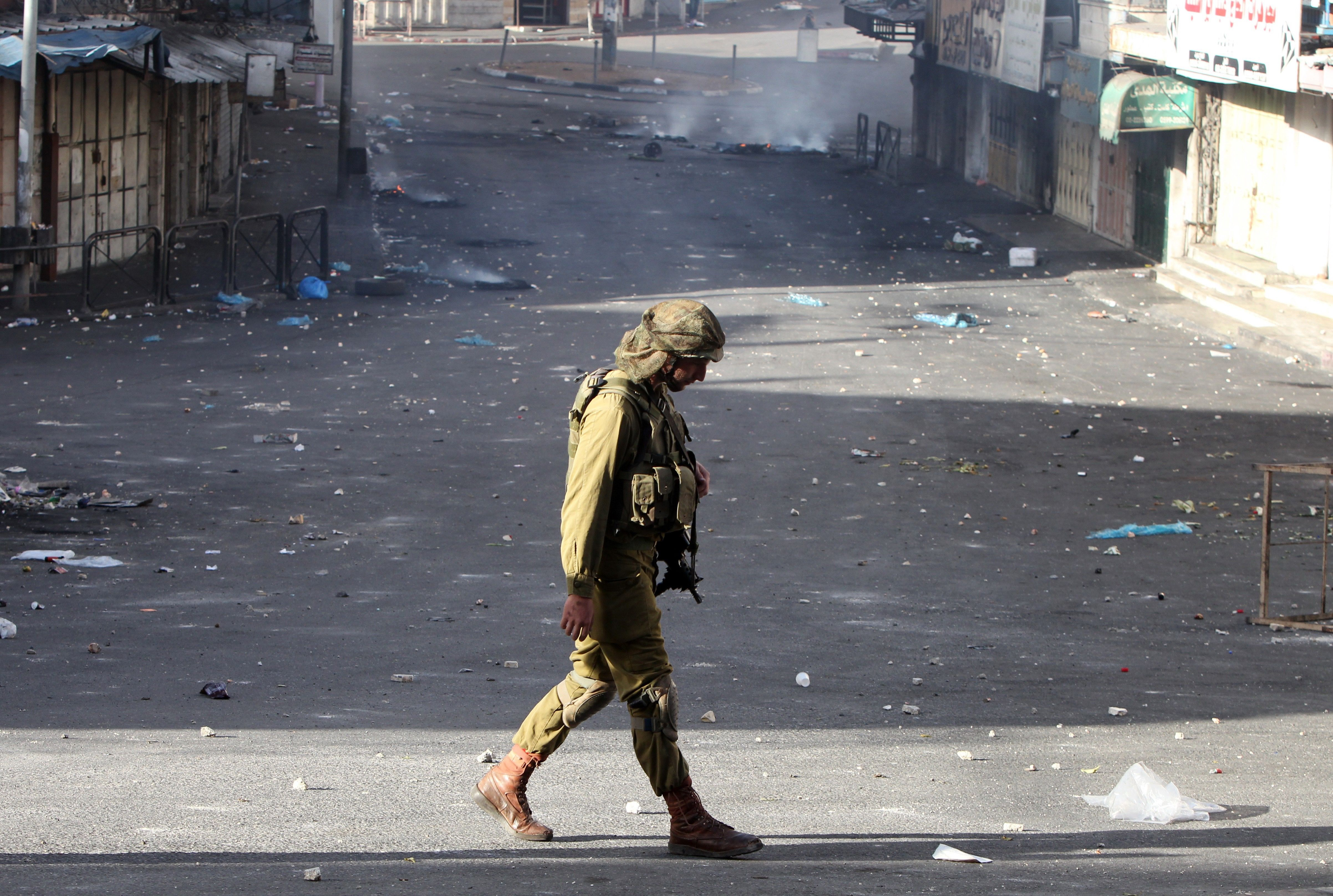 Israeli soldier walks through Hebron after clashes with Palestinians.