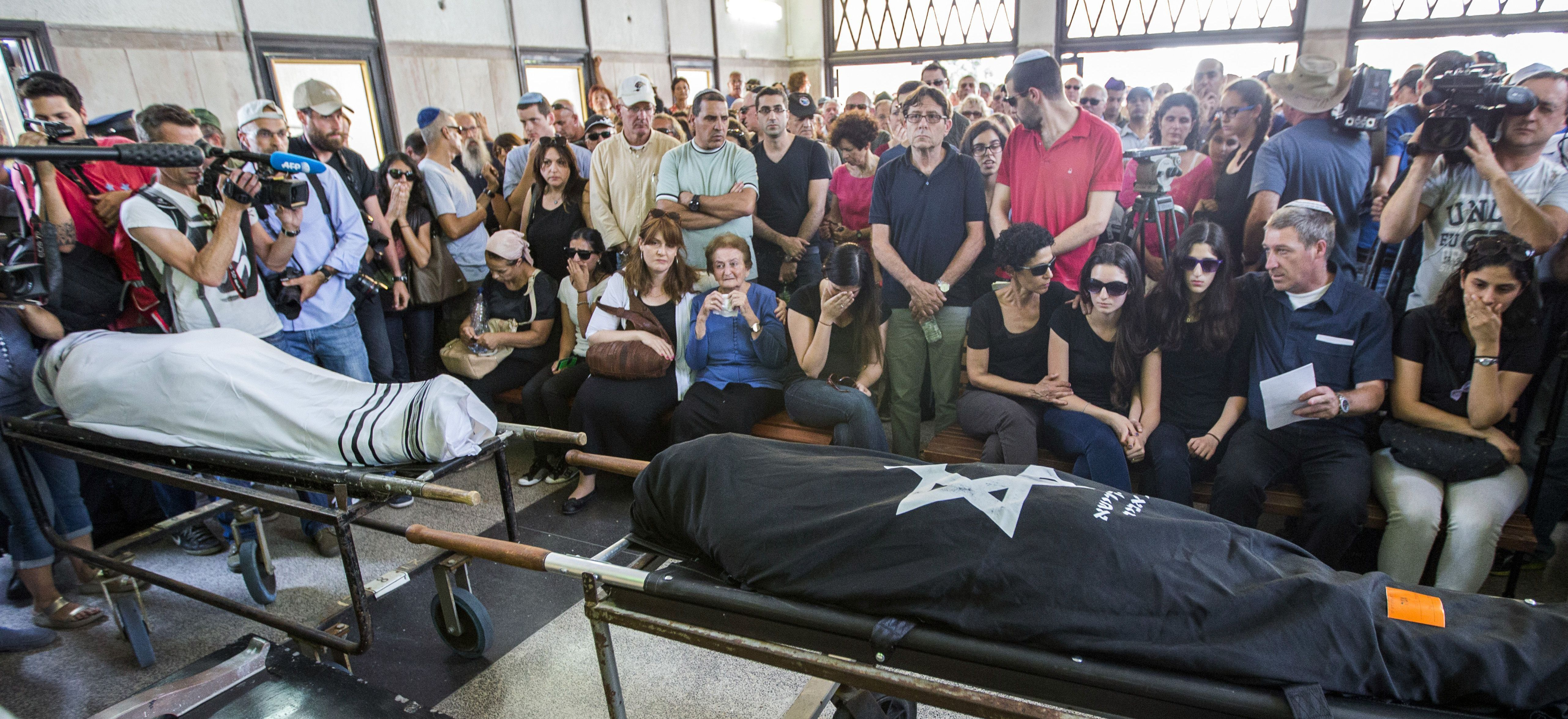 Relatives mourn over the bodies of Emanuel (L) and Miriam Riva (R), who were killed during the shooting attack at the Jewish Museum in the Belgian capital Brussels, during their funeral in Kyriat Shaul cemetery, Tel Aviv, on May 27, 2014.