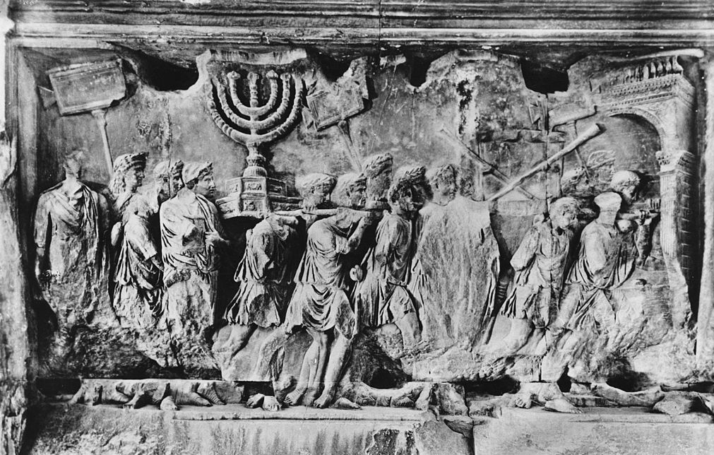 A relief from the Arch of Titus in Rome Italy, photographed circa 1955. The carving depicts spoils, including the Menorah and the trumpets of Jericho, being carried away from the Temple after the Siege of Jerusalem in 70 AD. The arch was built to commemorate the Roman emperor Titus Caesar Augustus, who had been the military commander responsible for the siege.