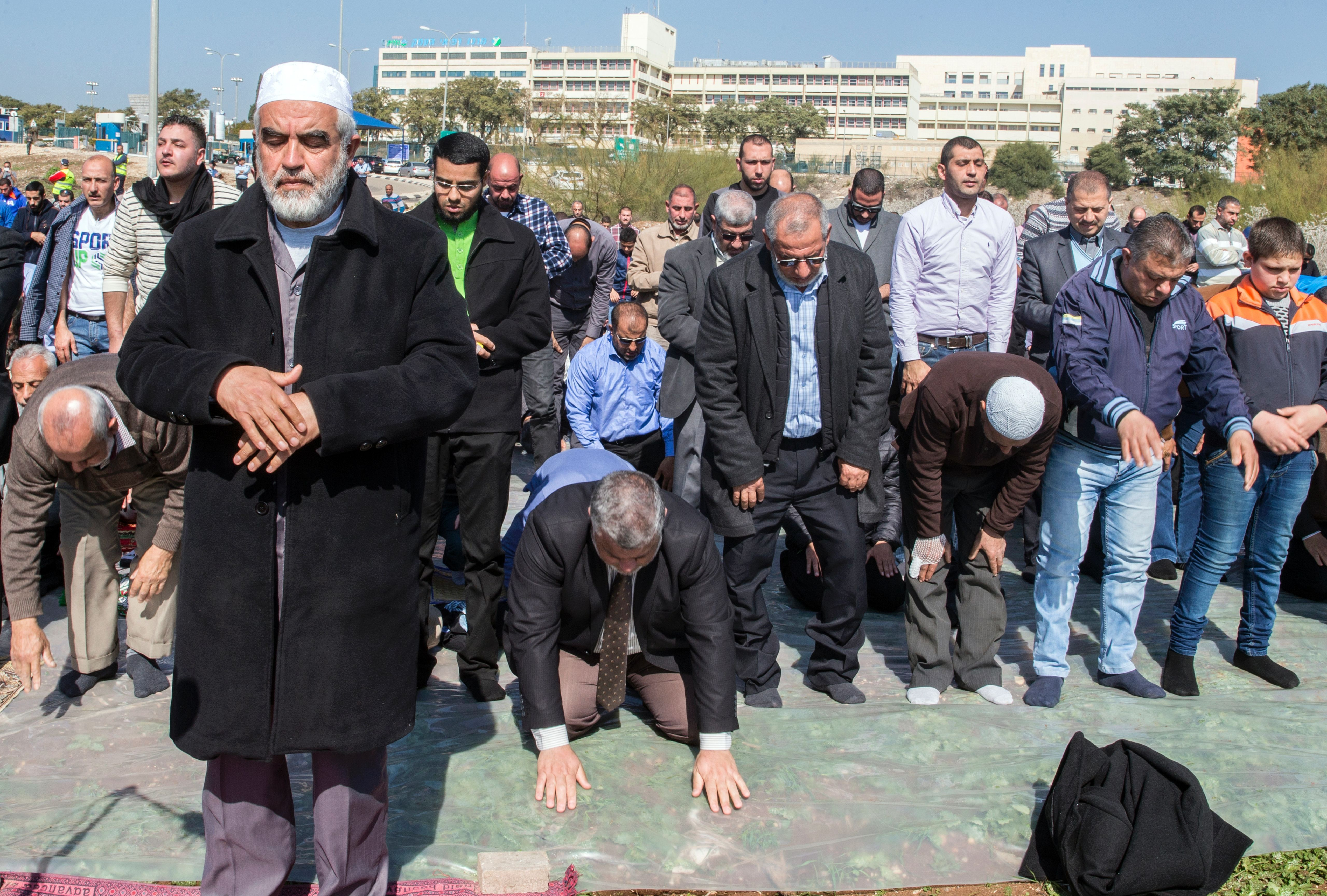 Israeli Arabs and Sheikh Raed Salah (front-L), the leader of the radical northern wing of the Islamic Movement in Israel, takes part in a prayer in support for the release of Mohammed al-Qiq, a Palestinian prisoner on hunger strike, outside the hospital where he is being treated in the northern Israeli town of Afula on February 12, 2016.