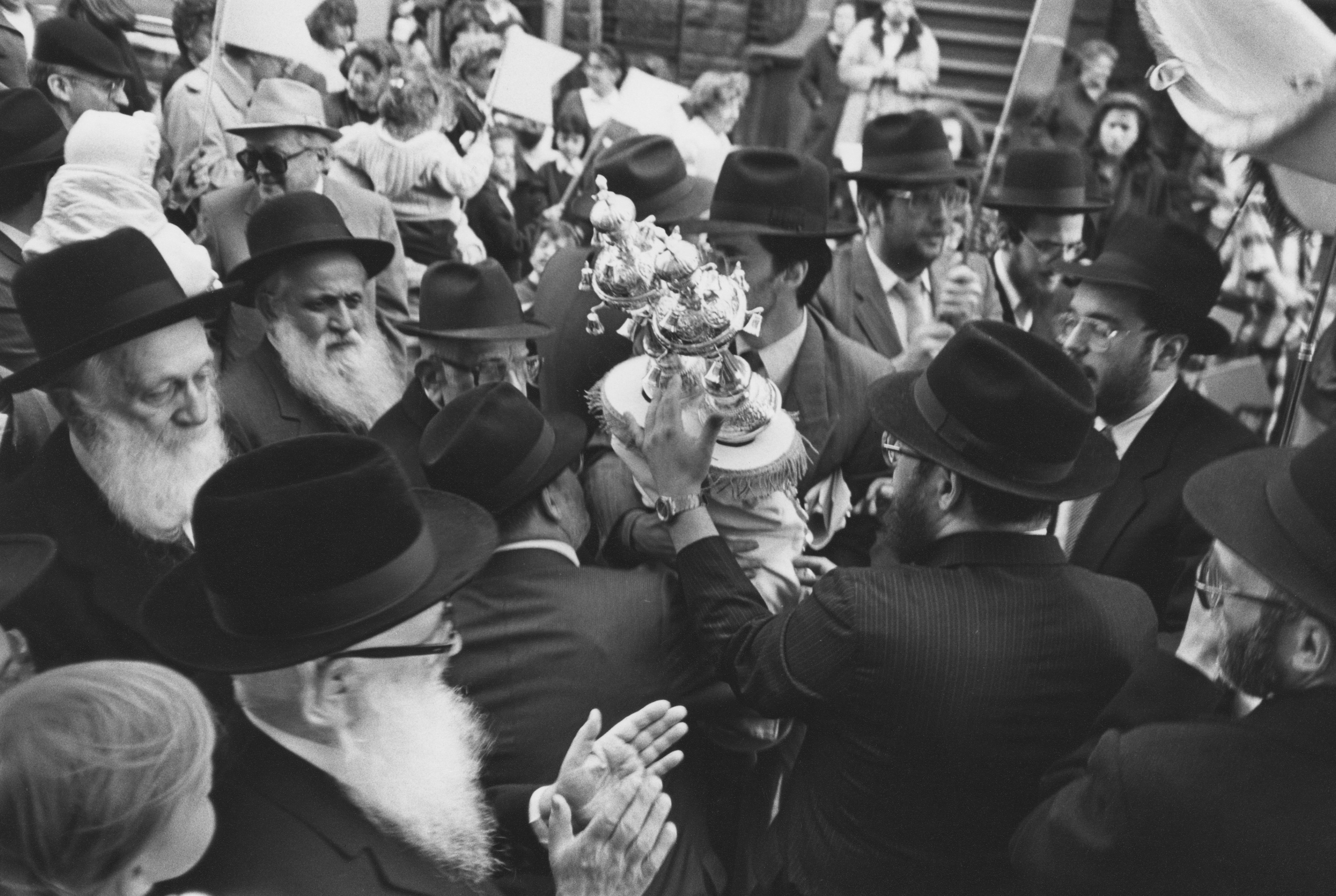The dedication of a new Torah scroll in a synagogue on the Upper West Side, New York City, 24th April 1988. The Torah is adorned with finial bells.