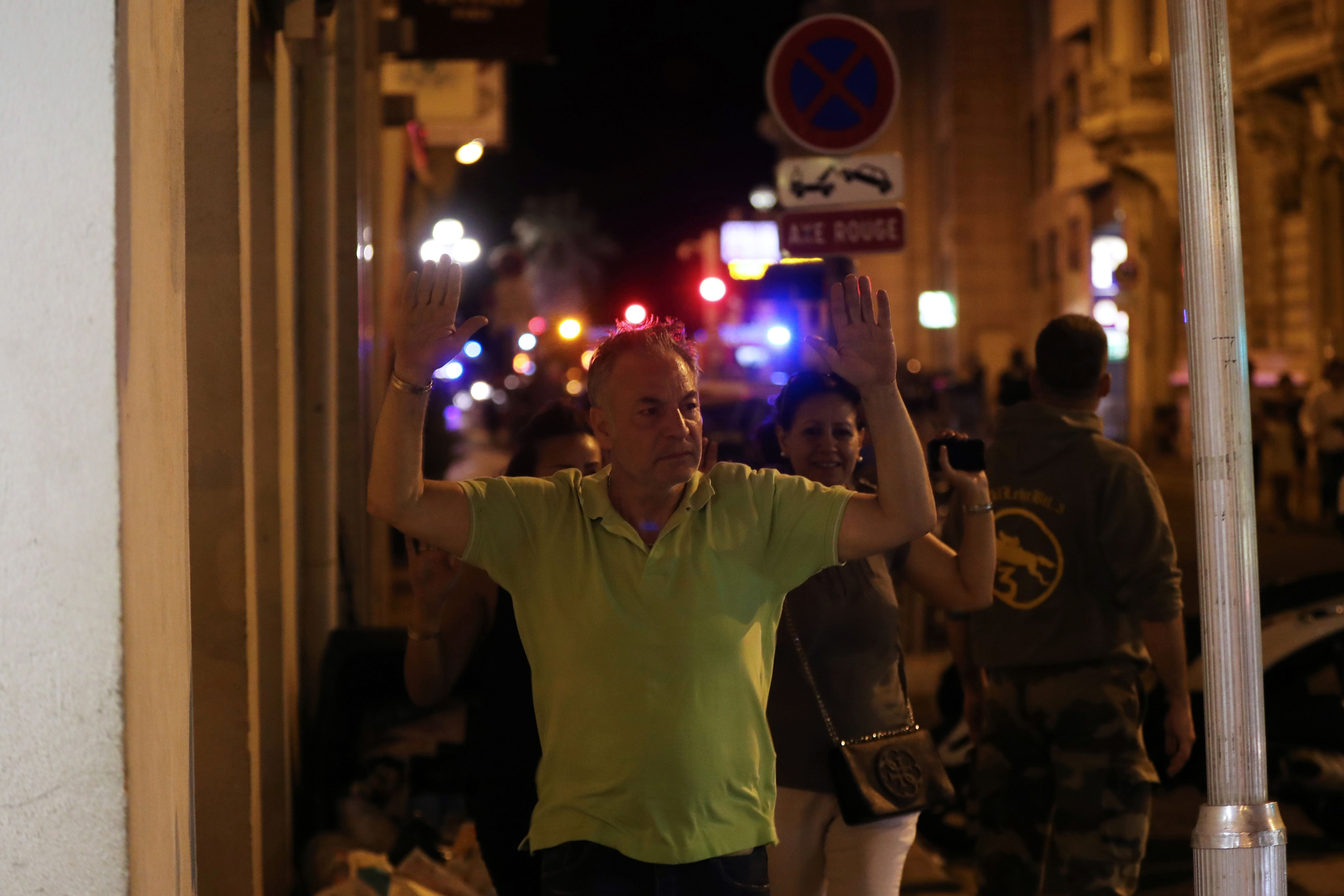 Bastille Day: A man raises his hands for police checks after a truck kills dozens in Nice, France.