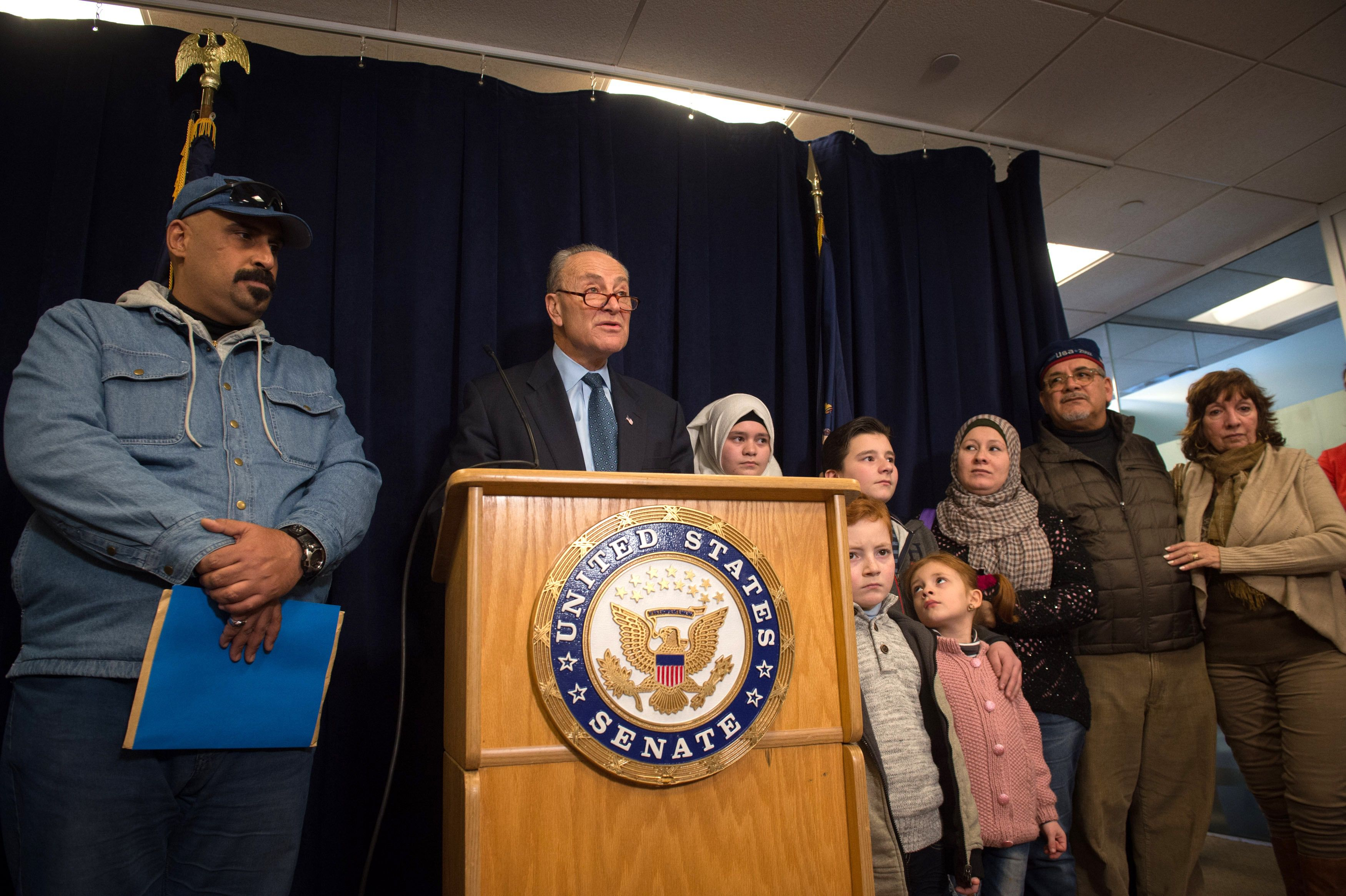 US Senator Charles Schumer stands with recently resettled refugees.
