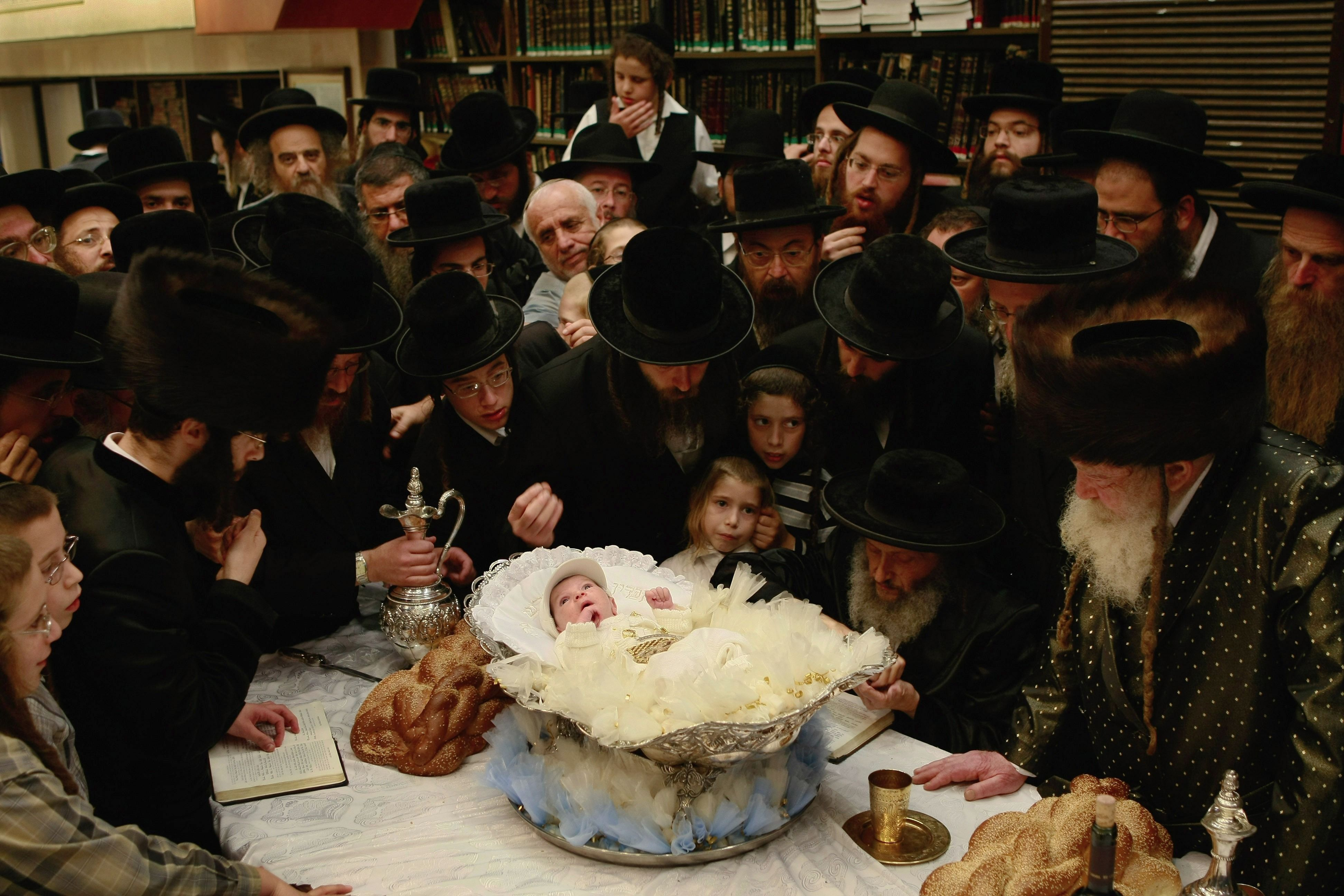 Ultra-Orthodox Jews pray over month-old infant Yehoshua Rosenboim, who lies in a silver bowl on the rabbi's table, as they perform the Redemption Of The First Born ceremony at the Lalov synagogue July 31, 2008 in Bnei Brak, Israel.