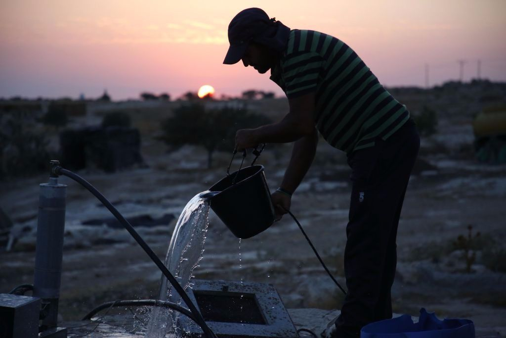 A Palestinian shepherd uses a bucket to get water from a well in the village of Susya south of the West Bank city of Hebron on August 19, 2017.