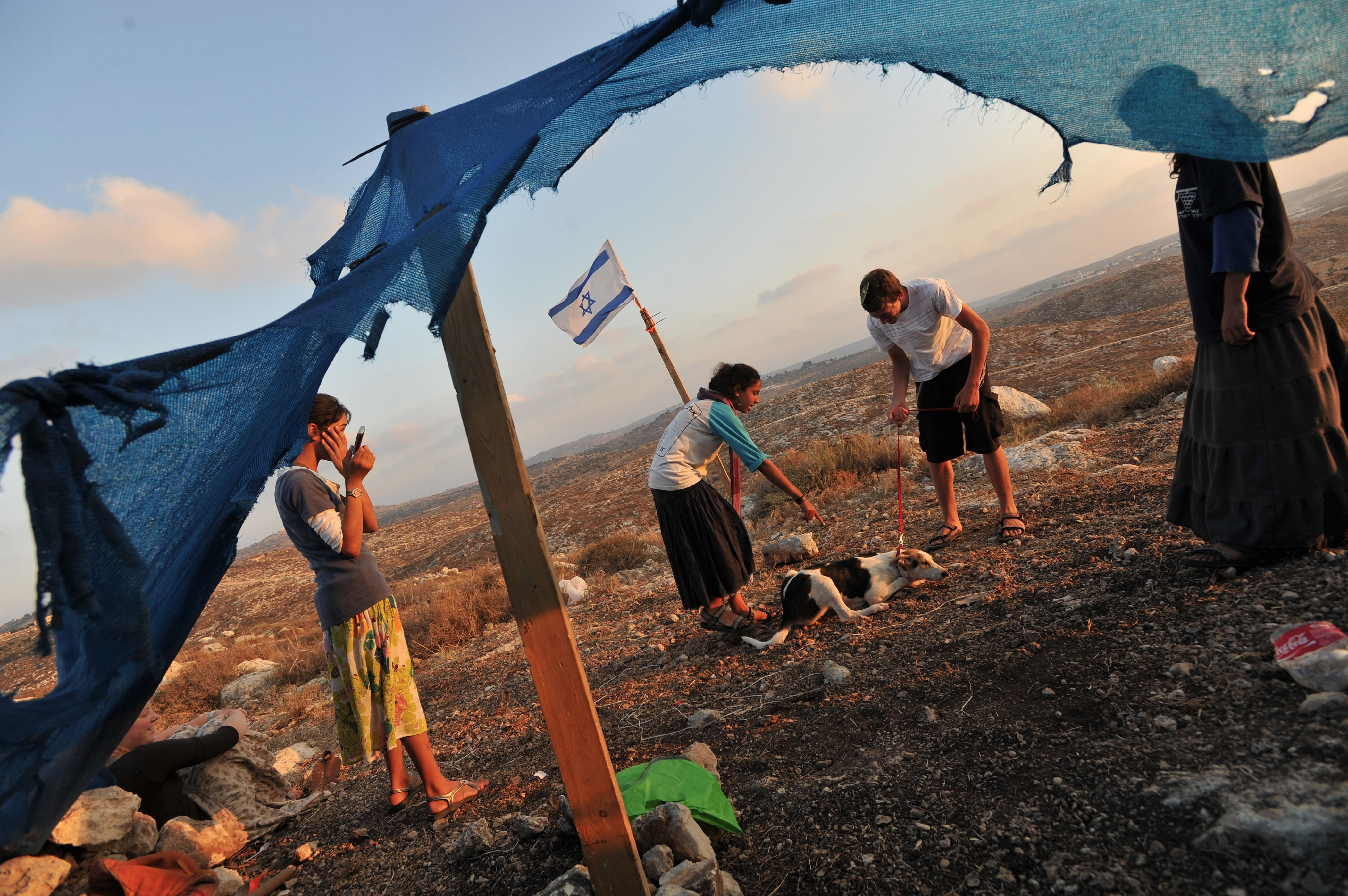 Young Jewish settlers play with a dog.