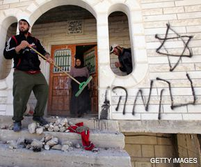 CLEANING UP: In the wake of a rampage by Jewish settlers, a man sweeps the porch of a Palestinian home near Hebron defaced with graffiti of Stars of David and the Hebrew word for ?revenge.?