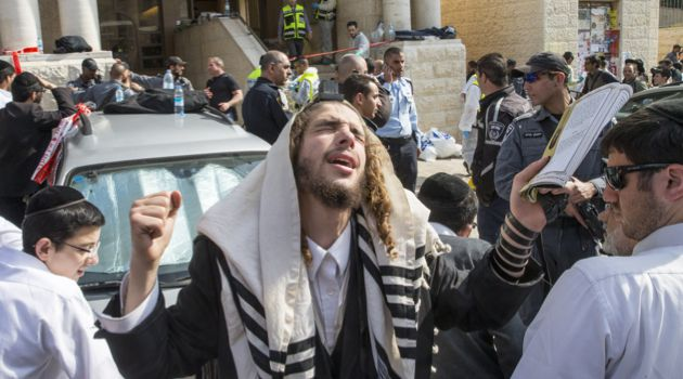 Crying Out: A man prays at the scene of the Har Nof attack.