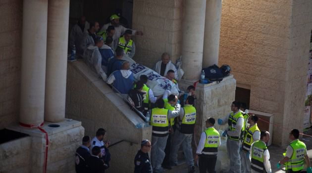 Israeli emergency personnel take out a body of an Israeli man outside a synagogue in Jerusalem after a deadly terror attack.