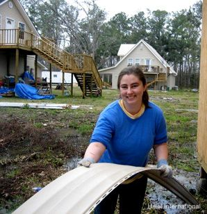BREAK TIME: On 'alternative breaks,' college students spend a week doing anything from teaching children to doing construction work on homes. Above, a student from Toronto puts siding on a damaged house in Mississippi.