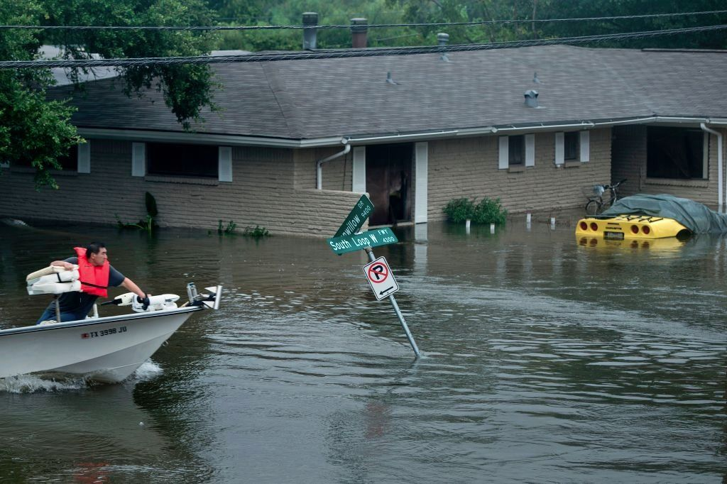 A boat passes through a flooded street during the aftermath of Hurricane Harvey in Houston, Texas.