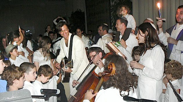 Surging: IKAR?s blend of joyful music and progressive politics is led by Rabbi Sharon Brous (with kiddush cup on right) and Hazan Hillel Tigay, playing guitar during havdallah after Yom Kippur services in 2011.