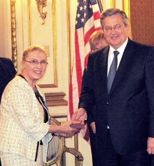 Masha Leon receiving the award from the President of Poland.