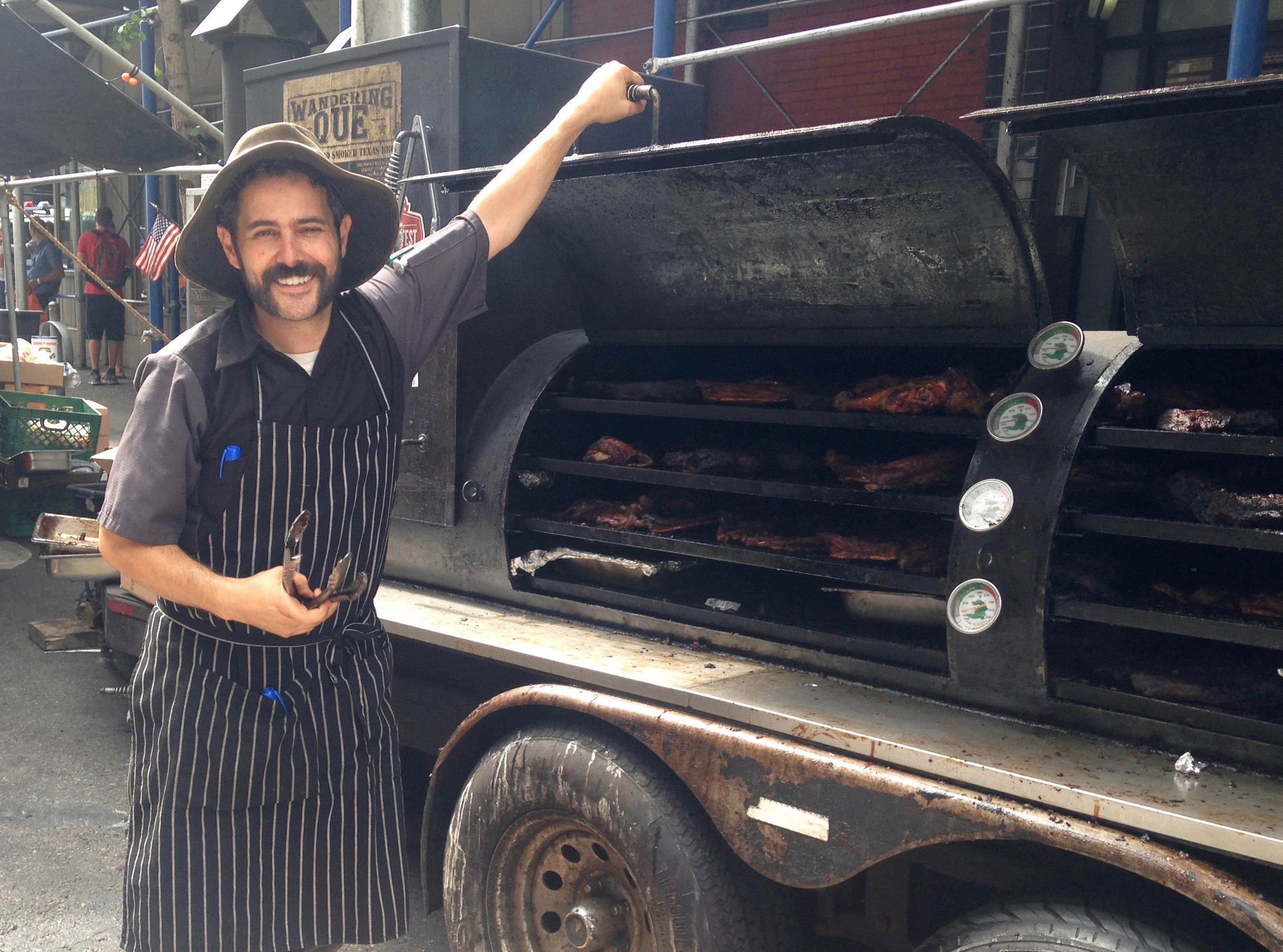 Ari White poses in front of his smoker at a street fair in Manhattan.