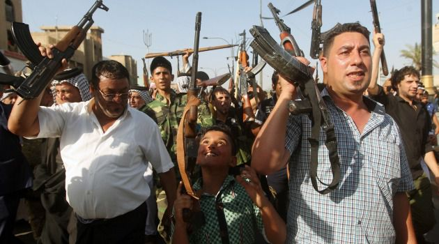 Uncertain Future:Iraqi boy and tribesmen hold up their weapons to join Iraqi security forces in the fight against Jihadist militants.