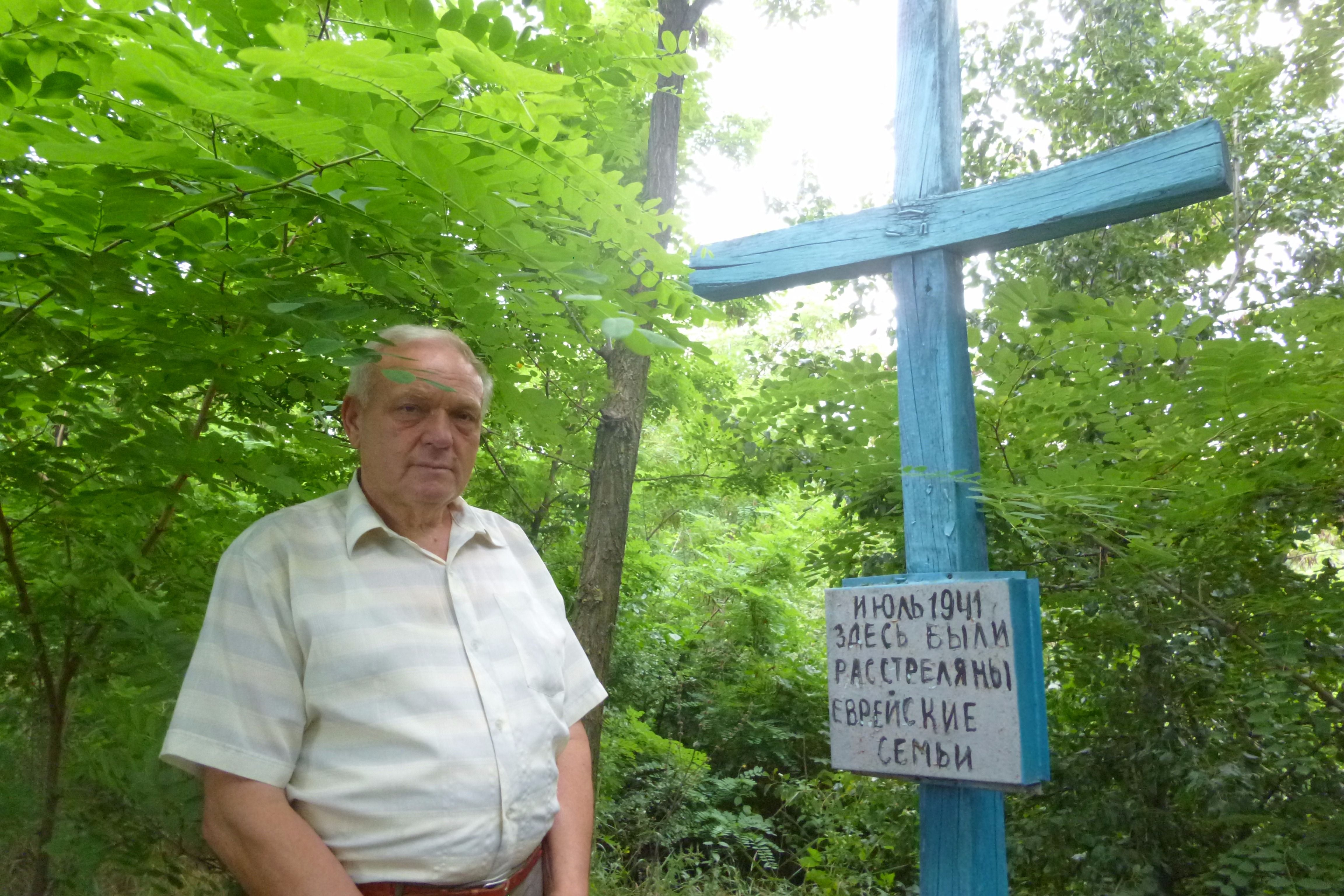 Educator Ivan Timoshko stands next to the memorial he built with his students for Jewish victims of the Holocaust massacre near his village.