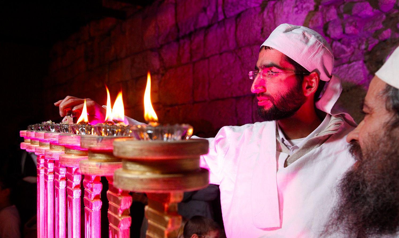 A member of the priestly Kohanic tribe lights a menorah.