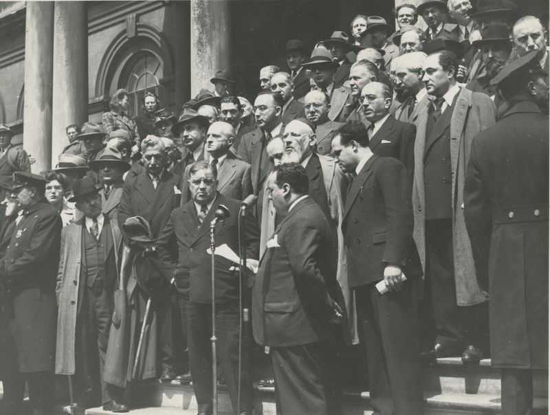 Thinking of Warsaw in New York: Dr. Joseph Thon speaks into the microiphone as Mayor La Guardia (left) listens. To the right of Dr. Thon is M.I. Nurenberger, Editor of the Canadian Jewish News, to his right is Senator Rabbi Isaac Rubinstein, former Chief Rabbi of Vilnius. Diagonally behind La Guardia is Yiddish writer Sholem Asch and next to him is Polish Jewish poet Julian Tuwim.
