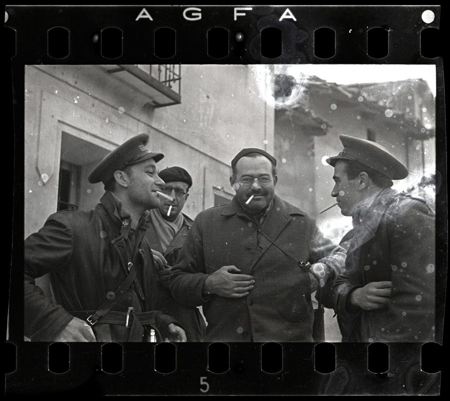 A Manful Fight: Ernest Hemingway (third from left), New York Times journalist Herbert Matthews (second from left) and two Republican soldiers smoke in Teruel, Spain, in 1937, in this photograph by Robert Capa. [CLICK FOR LARGER VIEW]