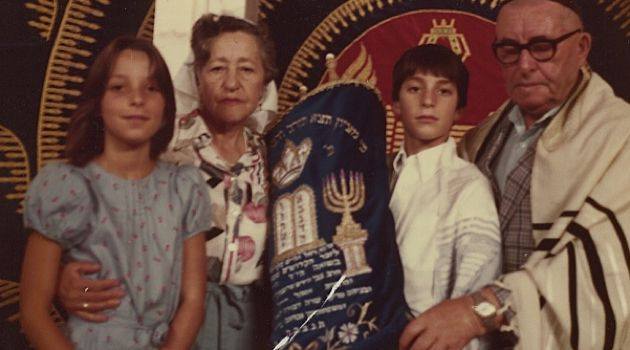 Generations: The author, her grandparents and brother pose with the Torah at her brother?s bar mitzvah in 1983, before the scroll disappeared.