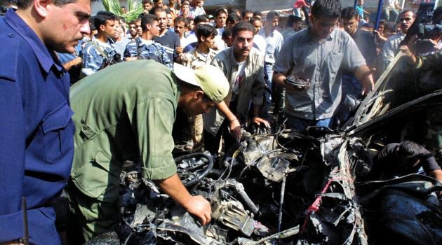 Palestinians inspect the wreckage of Hamas bomb expert, Mohammed Deif's car, after it was fired on by Israeli helicopter missiles in 2002.